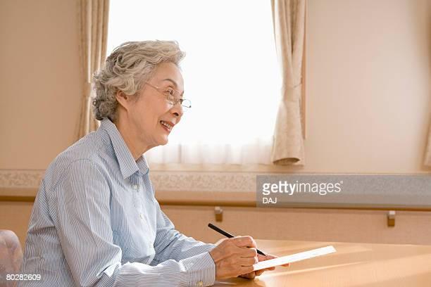 Senior woman making Japanese poem in hospital, smiling