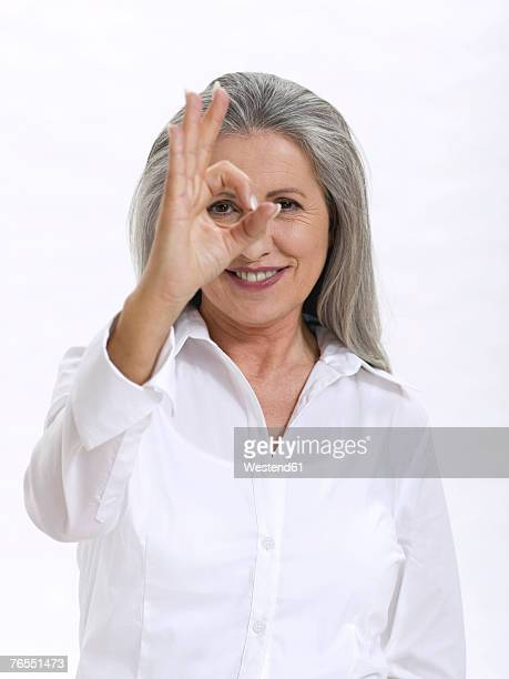 Senior woman making OK sign, close-up, portrait