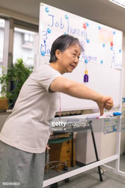 プレゼンテーション中に年配の女性を作って親指ダウン
