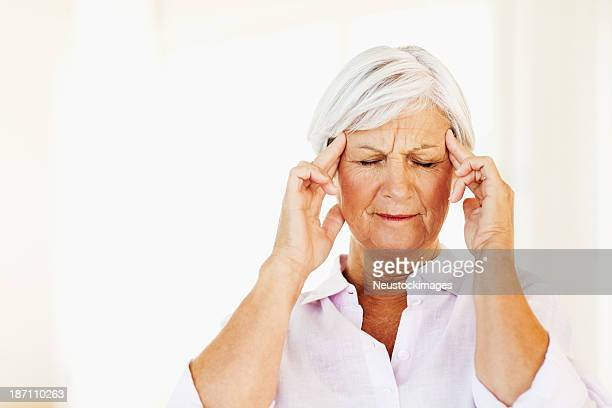 Senior Woman Massaging Temples While Suffering From Headache