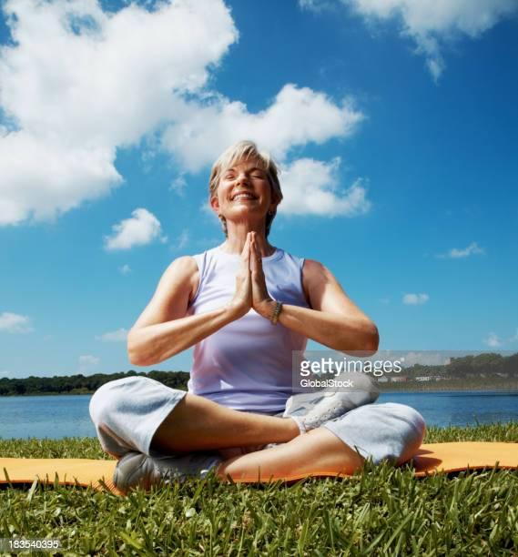 Senior woman meditating by meadow