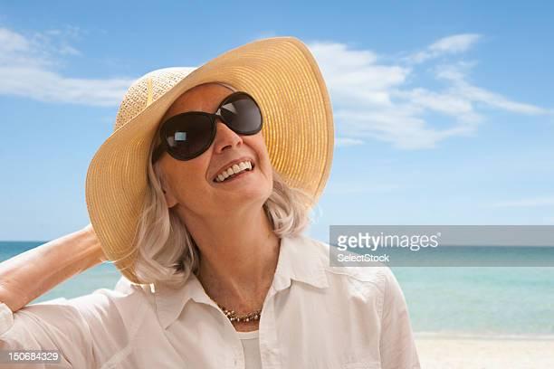 Senior woman on beach holding hat