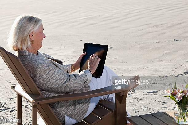Senior Femme sur la plage à l'aide de tablette numérique.