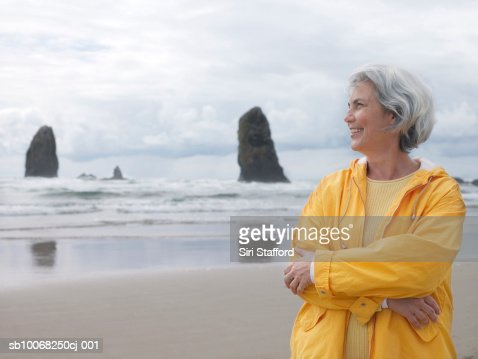 Senior woman on beach with arms crossed, smiling : Stock Photo