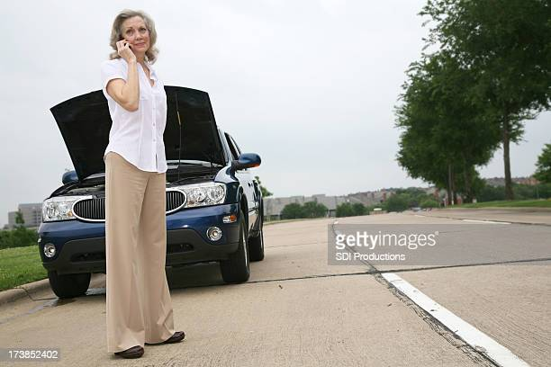 Senior Woman on her Cellphone by a Broken-down Car