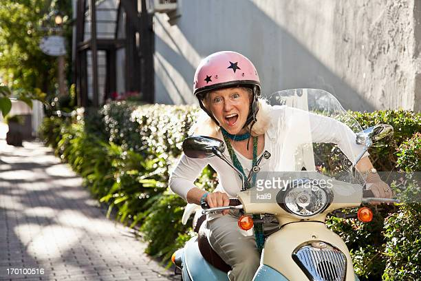 Senior woman on motor scooter