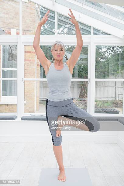 Senior woman on one leg in tree position doing yoga