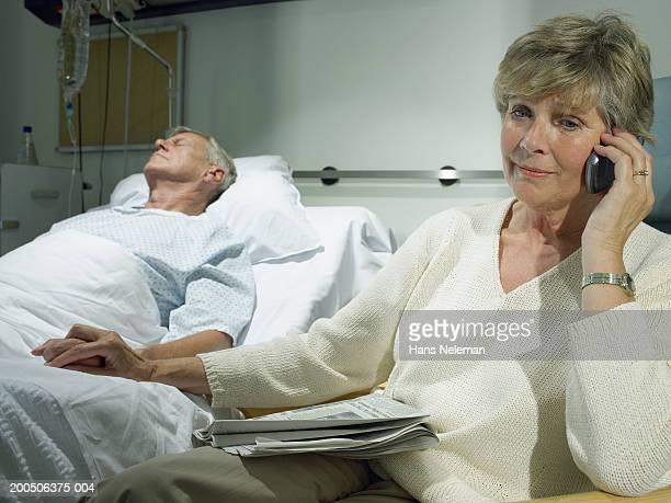 Senior woman on phone by senior man asleep in hospital bed