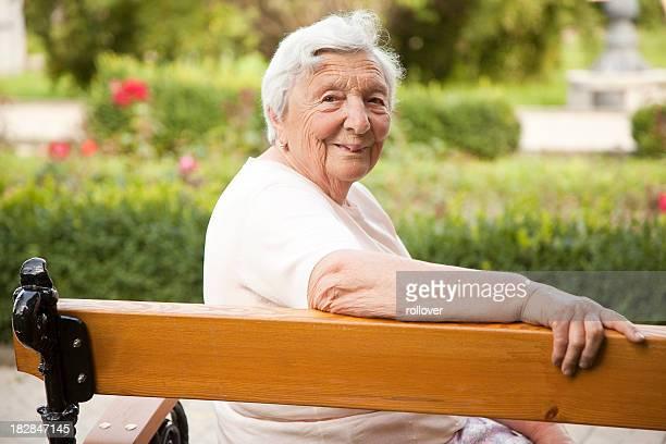 Femme âgée sur le banc dans le parc