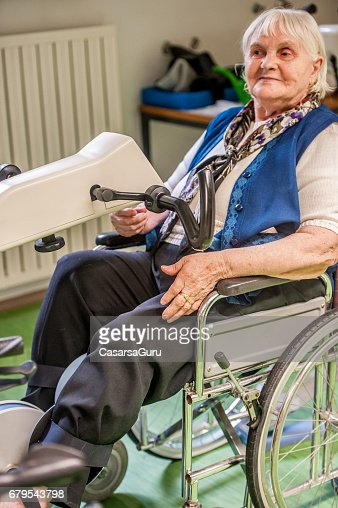 Senior Woman On Wheelchair Exercising On Exercise Bike Stock Photo