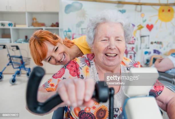Ältere Frau am Rollstuhl mit Physiotherapie auf Heimtrainer