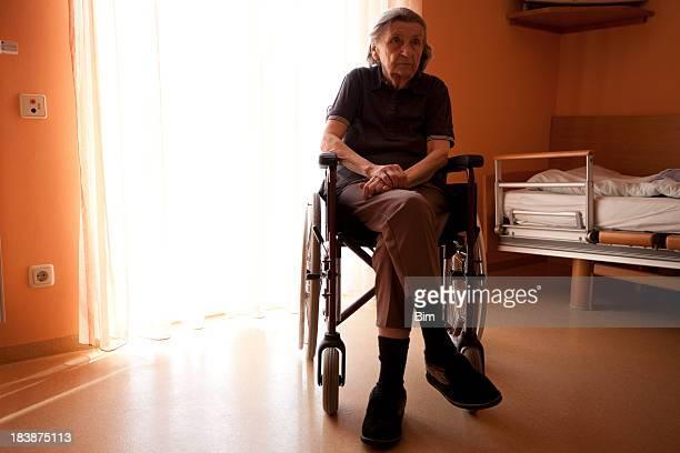Senior Frau auf einen Rollstuhl in einem Altersheim Zimmer