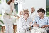 Senior woman on wheelchair tells jokes to her friend in white common room