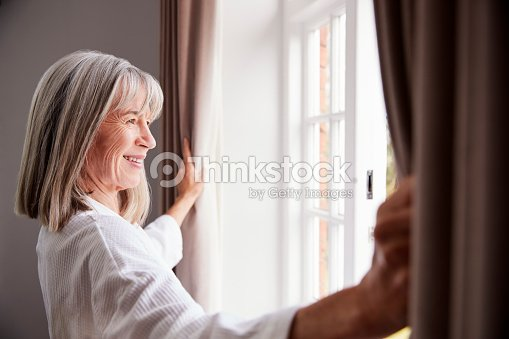 Senior Woman Opening Bedroom Curtains And Looking Out Of Window : Stock Photo