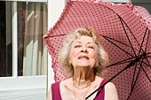Senior woman outdoors with pink parasol