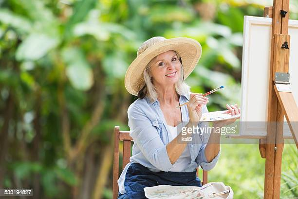 Senior woman painting a picture on canvas