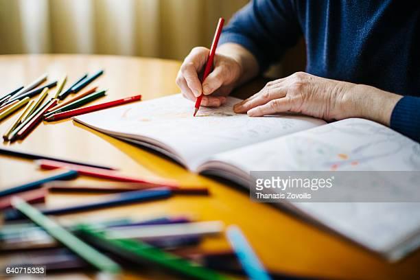 Senior woman painting a sketchbook