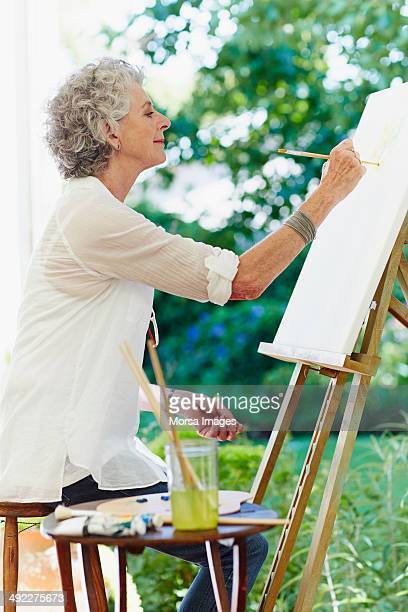 Senior woman painting in park