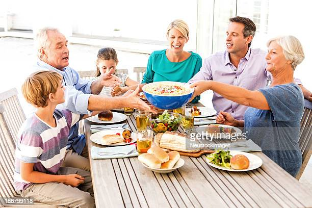 Senior Woman Passing Food While Having Lunch With Family Outdoor