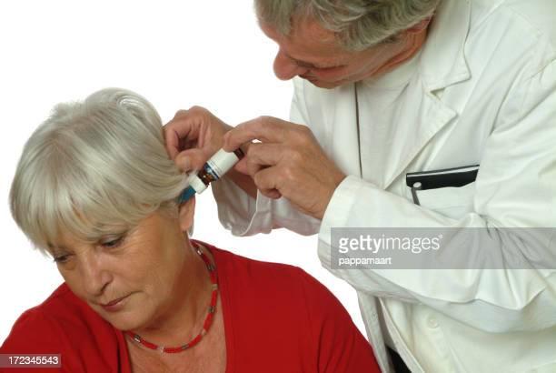 Senior Frau patient und Arzt Auftragen eardrops