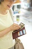 Senior woman paying cash