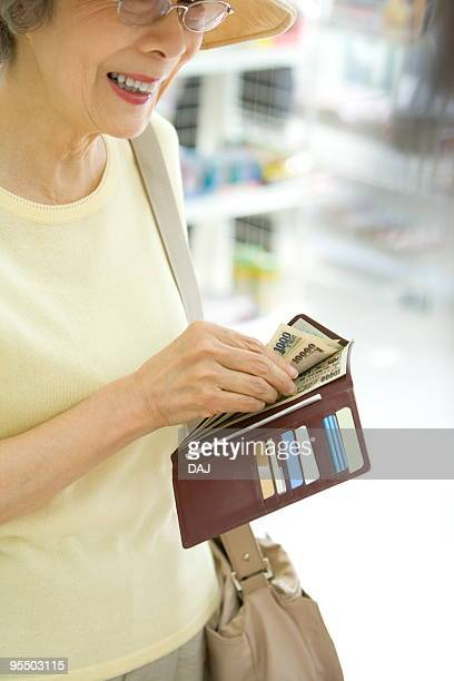 Senior woman paying cash
