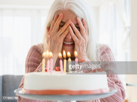 Senior woman peeking at candles on birthday cake : Stock Photo