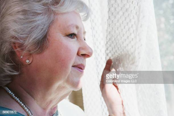 Senior woman peering out window