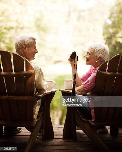 Senior Woman Photographing Her Husband in Adirondack Chairs