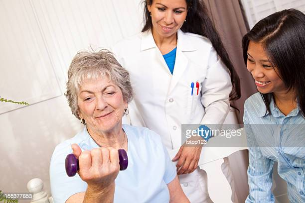 Senior woman. Physical therapy with doctor, family member. Lifting weights.