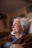 Senior Woman Lost in Thoughts Sitting Indoors.