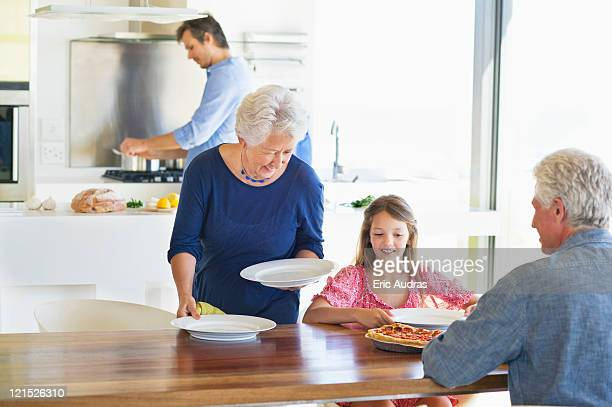 Senior woman placing plates on a dining table
