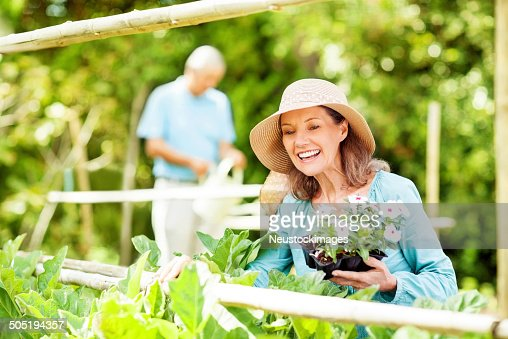 Senior Woman Planting Flowers While Man Watering In Garden