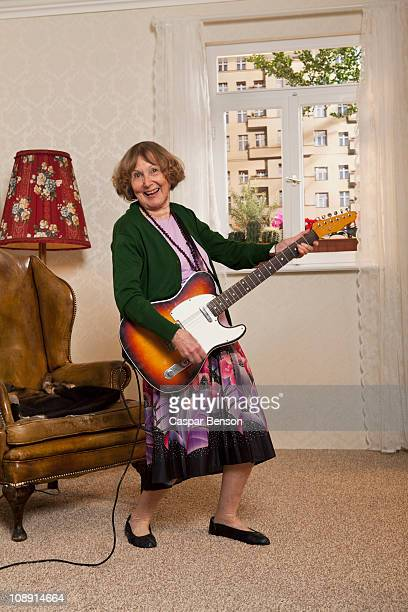 A senior woman playing an electric guitar