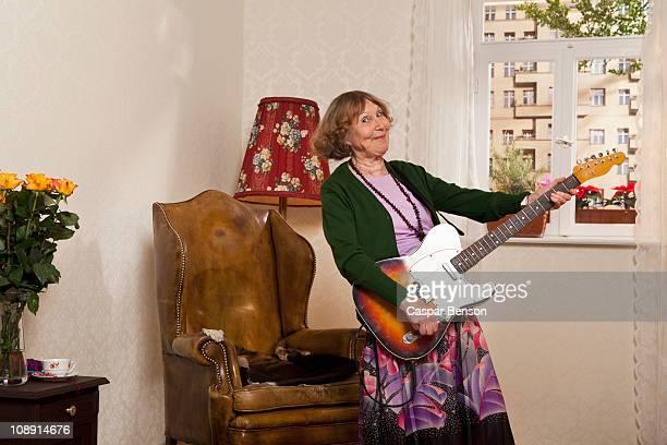 A senior woman playing an electric guitar