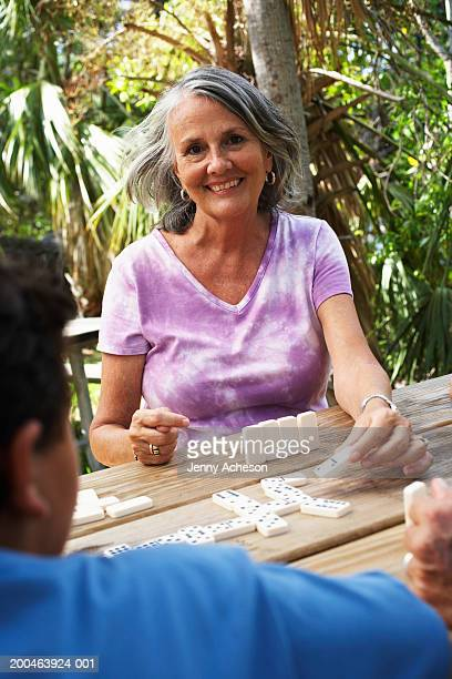 Senior woman playing dominoes at garden table, smiling, portrait