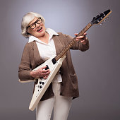 Happy funny senior woman playing electric guitar