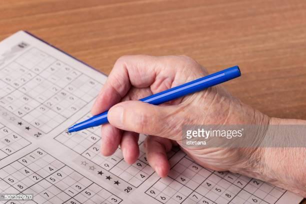 Senior woman playing in sudoku game