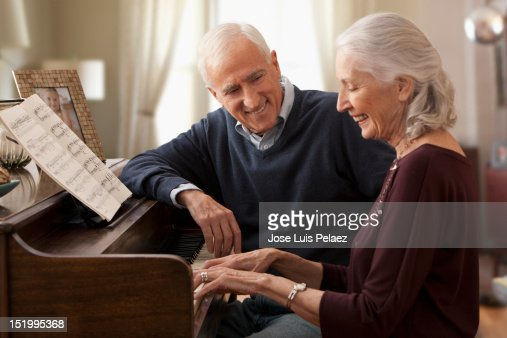 Senior woman playing piano for husband : Stock Photo