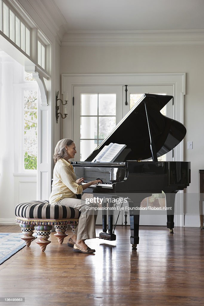 Senior woman playing piano : Stock Photo