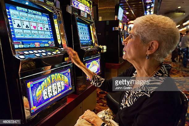 Senior woman playing slot machines