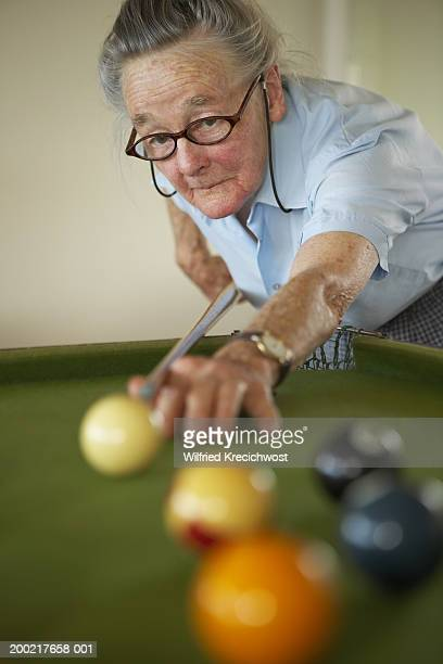 Senior woman playing snooker, holding cue to ball