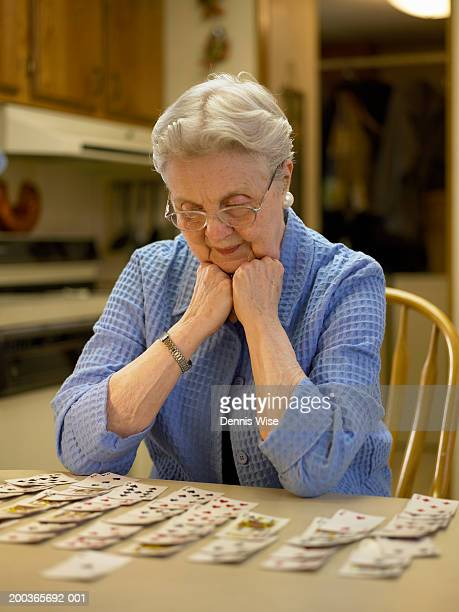 Senior woman playing solitaire, resting chin on hands