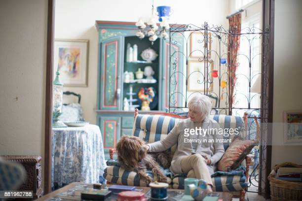 Senior woman playing with her dog at home