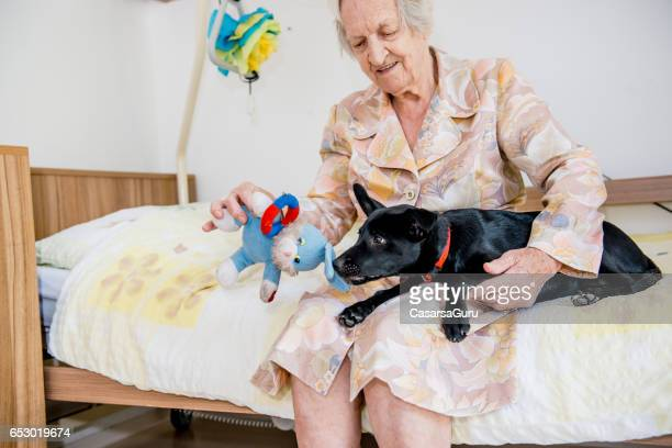 Senior Woman Playing With Her Dog In The Retirement Home