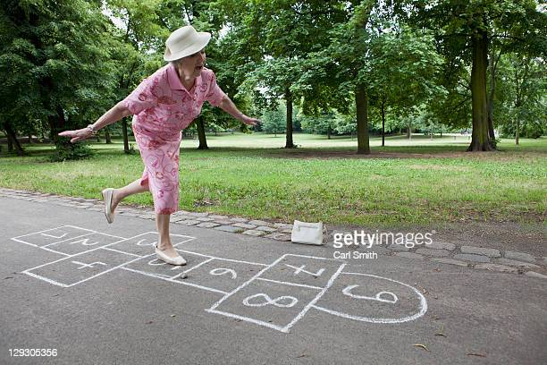 Senior woman plays hopscotch trying to keep her balance