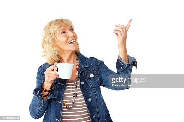 Senior woman pointing at copyspace with a cup of coffee