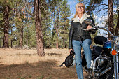 Senior woman poses with motorcycle in forest