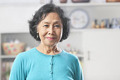 Senior Asian woman at home gazing to camera