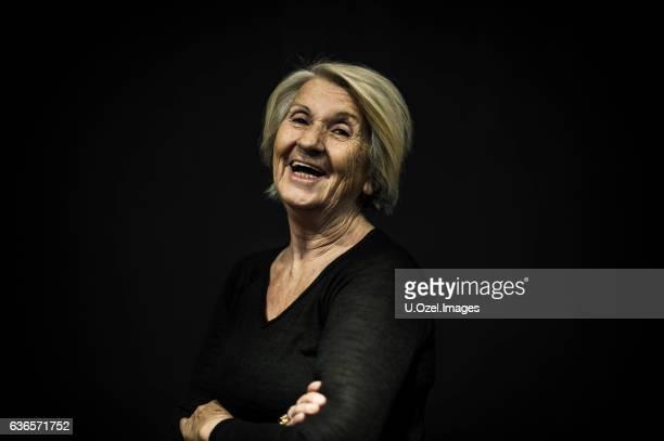Senior Woman Posing Front of a Black Wall